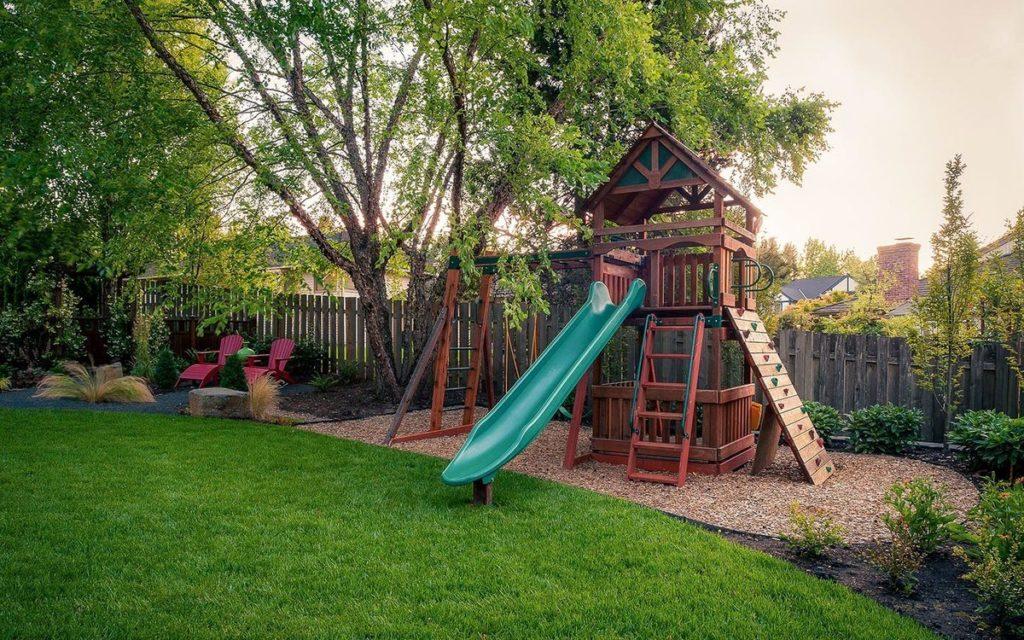 Защитить детскую площадку от сквозняков поможет декоративная ограда или живая изгородь